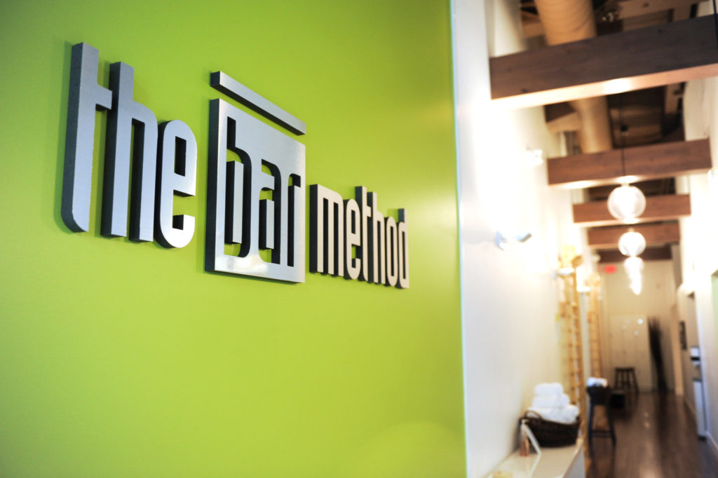 The Bar Method logo behind the front desk at The Bar Method Portland