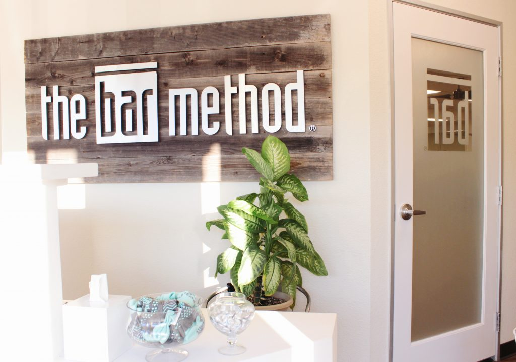 The Bar Method Logo Behind the Front Desk at the Bar Method Campbell